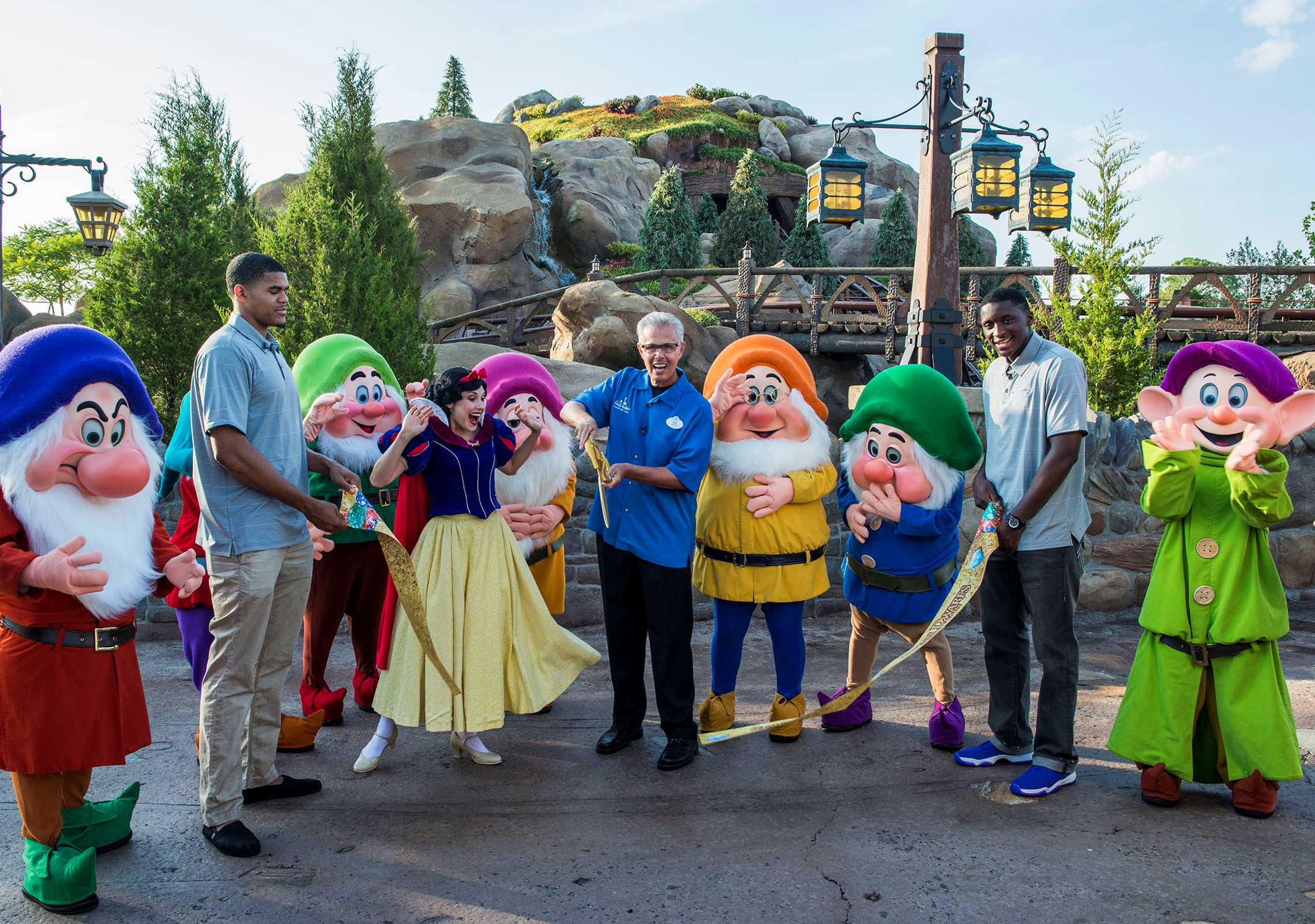 Snow White and the Seven Dwarfs join Phil Holmes (center), vice president of Magic Kingdom Park, and Orlando Magic players Tobias Harris (left) and Victor Oladipo (right)